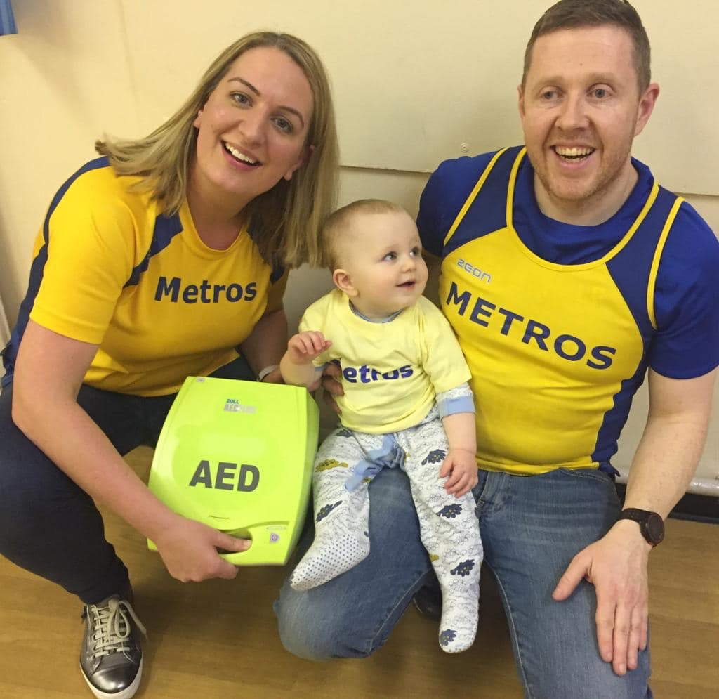 Picture of two people and a baby displaying the Metros defibrillator